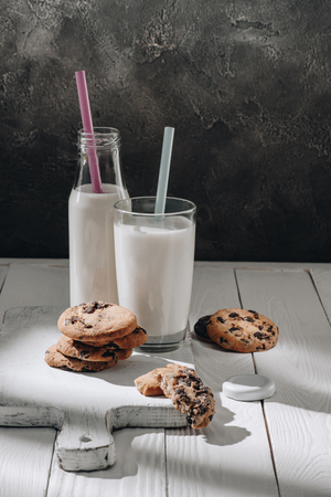 Chocolate-chip cookies on white wooden cutting board with milk Foto de archivo - 110952180