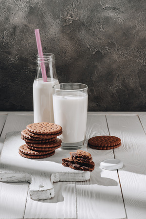 Stack of delicious cookies with glass and bottle of milk on white wooden table Foto de archivo - 110952192
