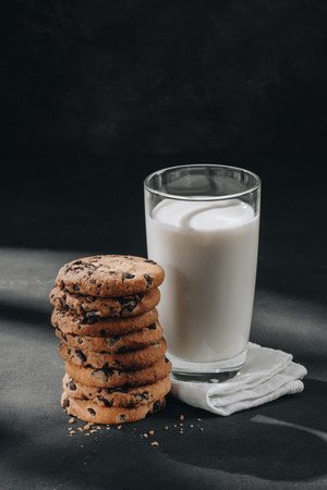 Stack of chocolate-chip cookies with glass of milk on black surface Foto de archivo - 110952136