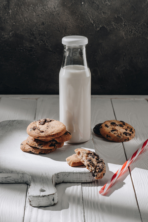 Delicious chocolate-chip cookies with bottle of milk on wooden board Foto de archivo - 110952140