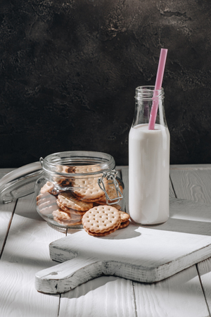Delicious cookies in glass jar with bottle of milk