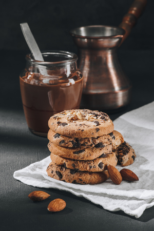 Delicious chocolate-chip cookies with jar of chocolate mousse and jezve Foto de archivo - 110952144