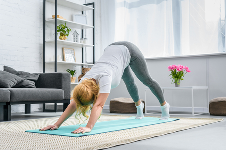 Woman in downward facing dog position on yoga mat 스톡 콘텐츠