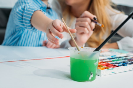 Cropped image of mother and son dipping paintbrush into colored water