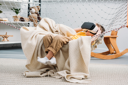 Little boy laying in rope hammock and using virtual reality headset Stock Photo