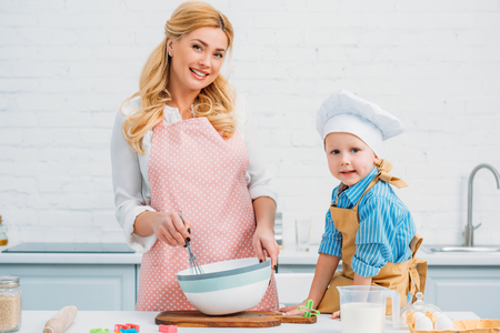 Little boy and mother cooking together in kitchen Фото со стока