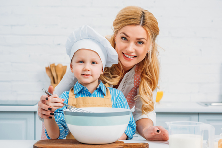 Mother holding son while he using hand beater