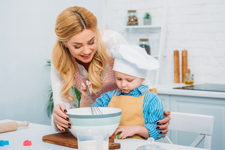 Happy mother holding son while he using hand beater