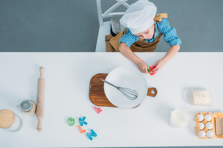 Top view of little boy in cooking hat sitting at table with kitchenware and ingredients