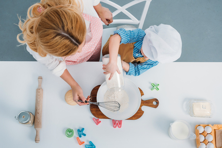 Top view of mother and boy pouring milk into bowl with egg and flour Фото со стока