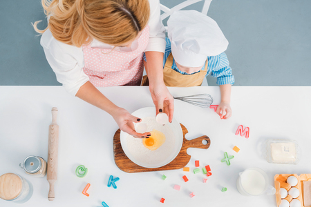 Top view of mother and son pouring egg into bowl with flour