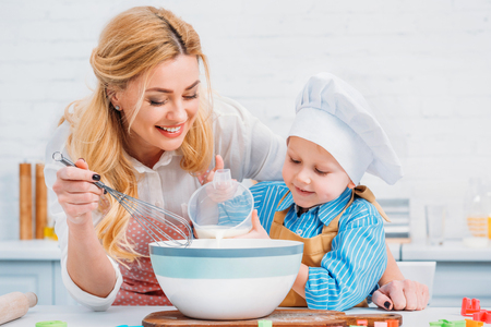 Mother with hand beater and little boy pouring milk into bowl