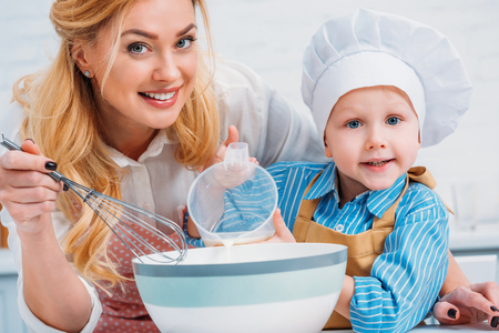 Happy mother with hand beater and little boy pouring milk into bowl Фото со стока