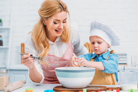 Smiling mother with hand beater and little boy pouring egg into bowl