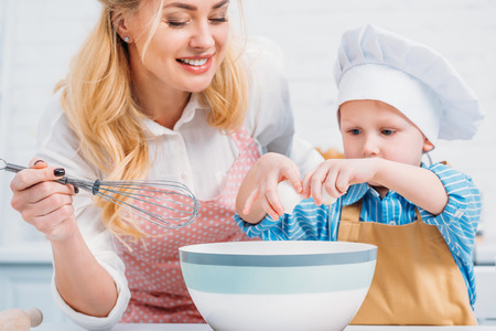 Mother with hand beater and little boy pouring egg into bowl Фото со стока
