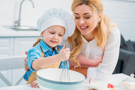 Smiling mother embracing little son while he using hand beater
