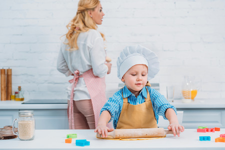Little boy rolling dough and mother standing behind in kitchen Stock Photo