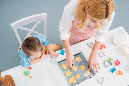 High angle view of son and mother putting dough for cookies on baking sheet