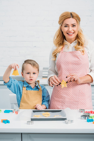 Happy mother and son holding figured dough for cookies Stock fotó