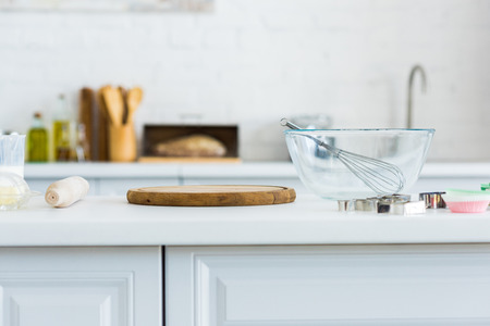 Rolling pin, cutting board and bowl with whisk on kitchen counter
