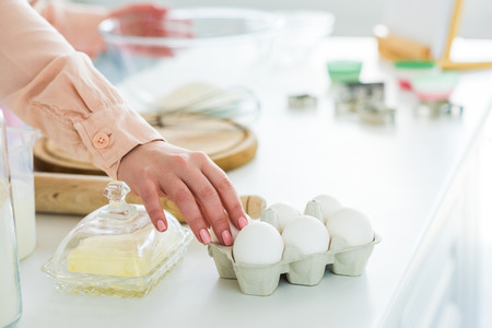 Cropped image of woman taking eggs for dough at kitchen