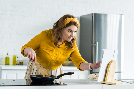 Beautiful woman looking at recipe book and frying vegetables on frying pan at kitchen