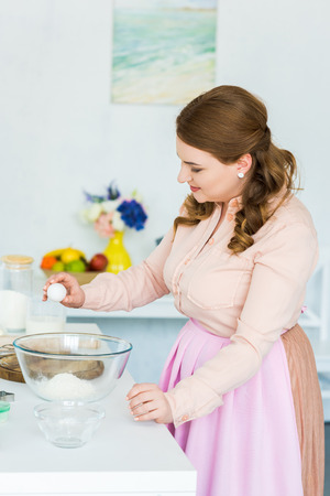 Side view of beautiful woman breaking egg for dough in kitchen