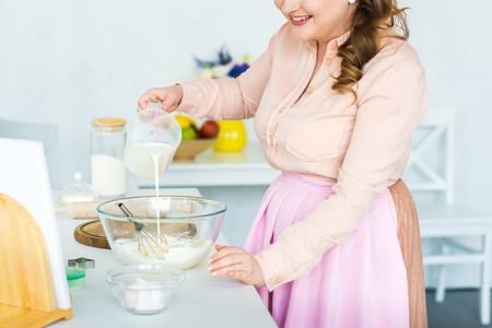Cropped image of woman pouring milk into bowl with flour at kitchen