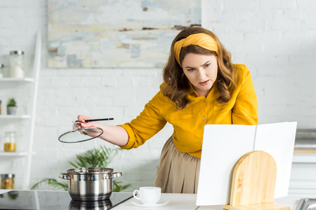 Beautiful woman cooking and reading recipe book in kitchen Stock Photo