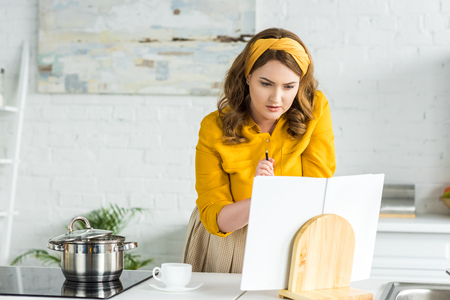 Beautiful woman reading recipe book in kitchen Stock Photo