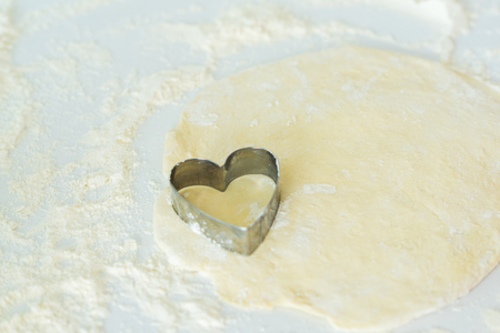 One heart shaped cookie cutter on dough