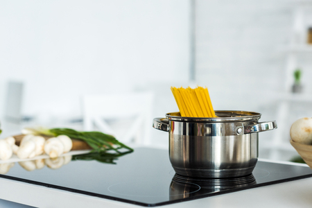 Pan with pasta on clean electric stove in kitchen