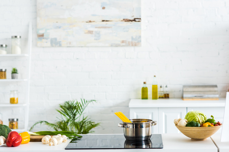 Interior of modern light kitchen with paint on wall and electric stove