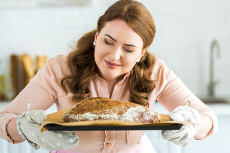 Beautiful woman sniffing homemade loaf of bread at kitchen
