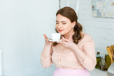 Beautiful woman sniffing coffee with closed eyes in kitchen