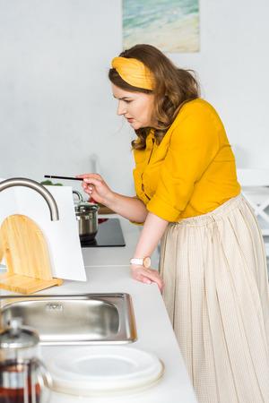 Beautiful woman reading recipe in recipe book in kitchen