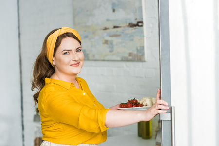 Beautiful woman holding plate with vegetables at kitchen