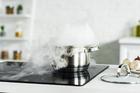 Dampf über der Pfanne auf dem Elektroherd in der Küche Standard-Bild