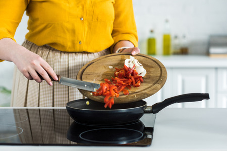 Cropped image of woman pouring out vegetables into frying pan at kitchen