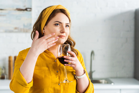 Beautiful woman smelling red wine in kitchen