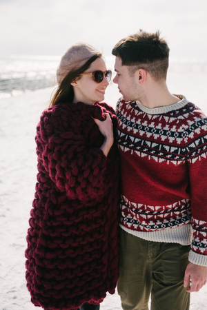 Stylish young couple smiling and hugging on quay at winter Stock Photo