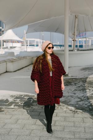 Stylish young woman in burgundy merino wool cardigan walking on quay