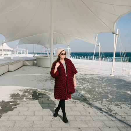 Beautiful girl in sunglasses and burgundy merino wool cardigan walking on quay 스톡 콘텐츠