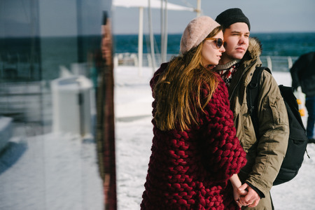 Stylish young couple holding hands on quay at winter Фото со стока