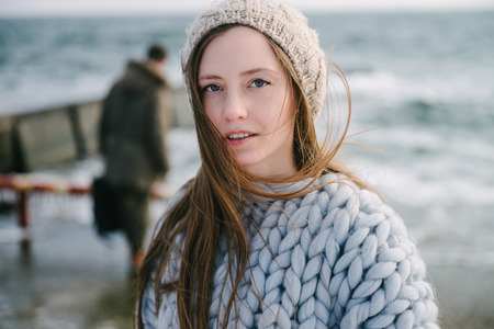 Attractive young woman in merino wool sweater and hat on winter seashore Archivio Fotografico - 111004541