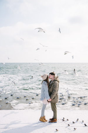 Young couple holding hands and kissing on seashore in winter Фото со стока