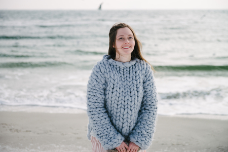 Beautiful smiling girl in merino wool sweater on winter seashore Archivio Fotografico - 111004465