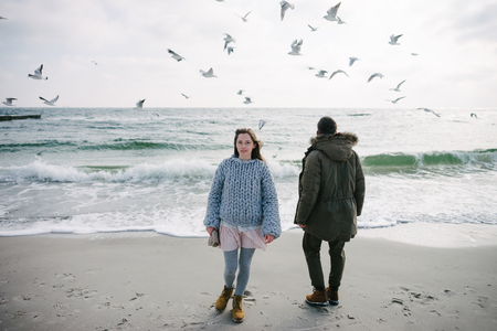 Young couple standing on winter sea shore with seagulls Фото со стока - 111004462