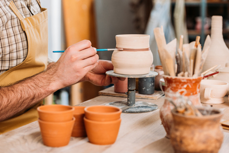 Cropped view of potter painting ceramic jug with brush in workshop Stok Fotoğraf