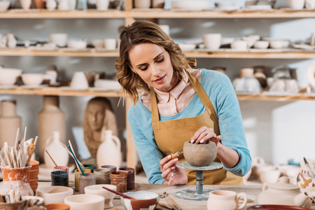 Beautiful female potter decorating ceramic bowl in workshop